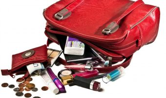 Red purse on its side with contents spilling out