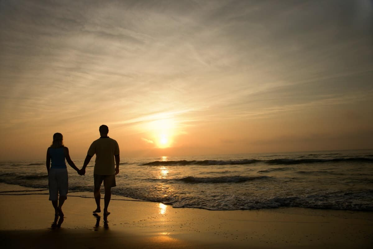 Couple holding hands walking away from the camera on the beach at sunset