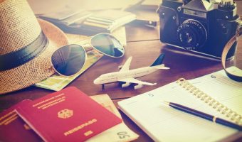 Travel items for vacation on a table including camera, journal, passport, money, sunglasses, wallet and straw hat