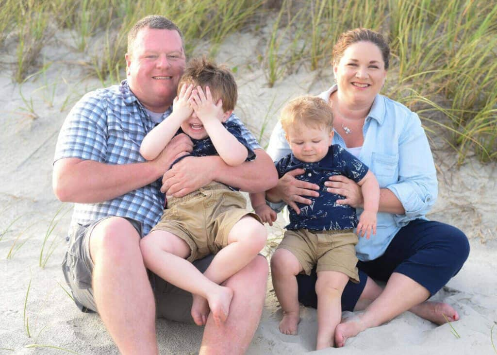 Mother and Father with two toddler boys in posed picture on the beach
