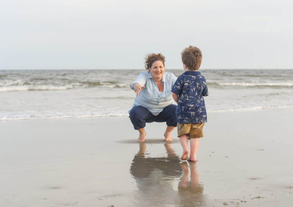 Toddler running to mom on the beach