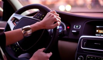 woman driving nice car at sunset with silver cuff bracelet