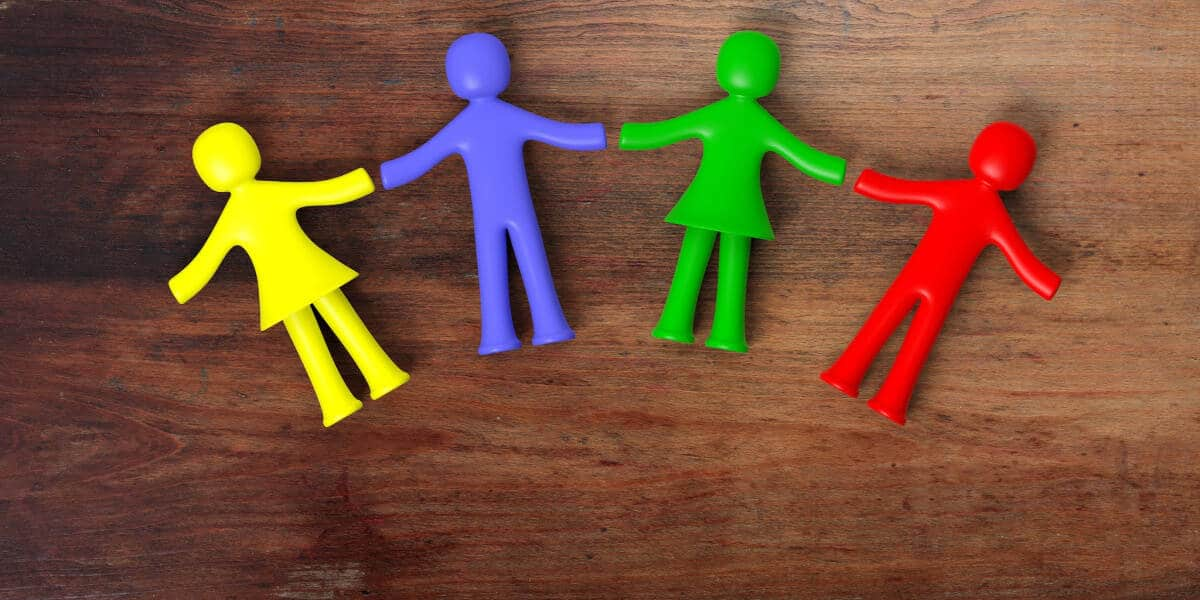 Wooden table background with 4 colorful figures holding hands