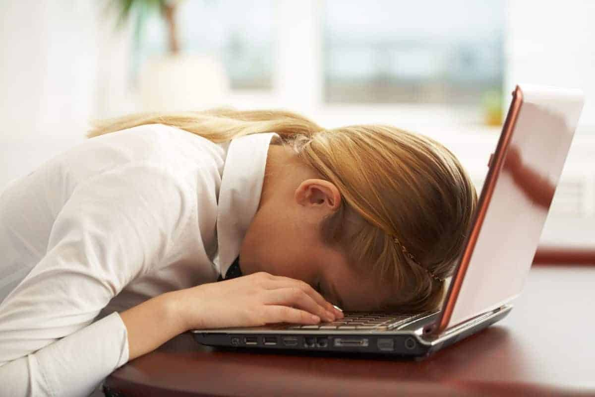 woman having a bad day with face down on her laptop