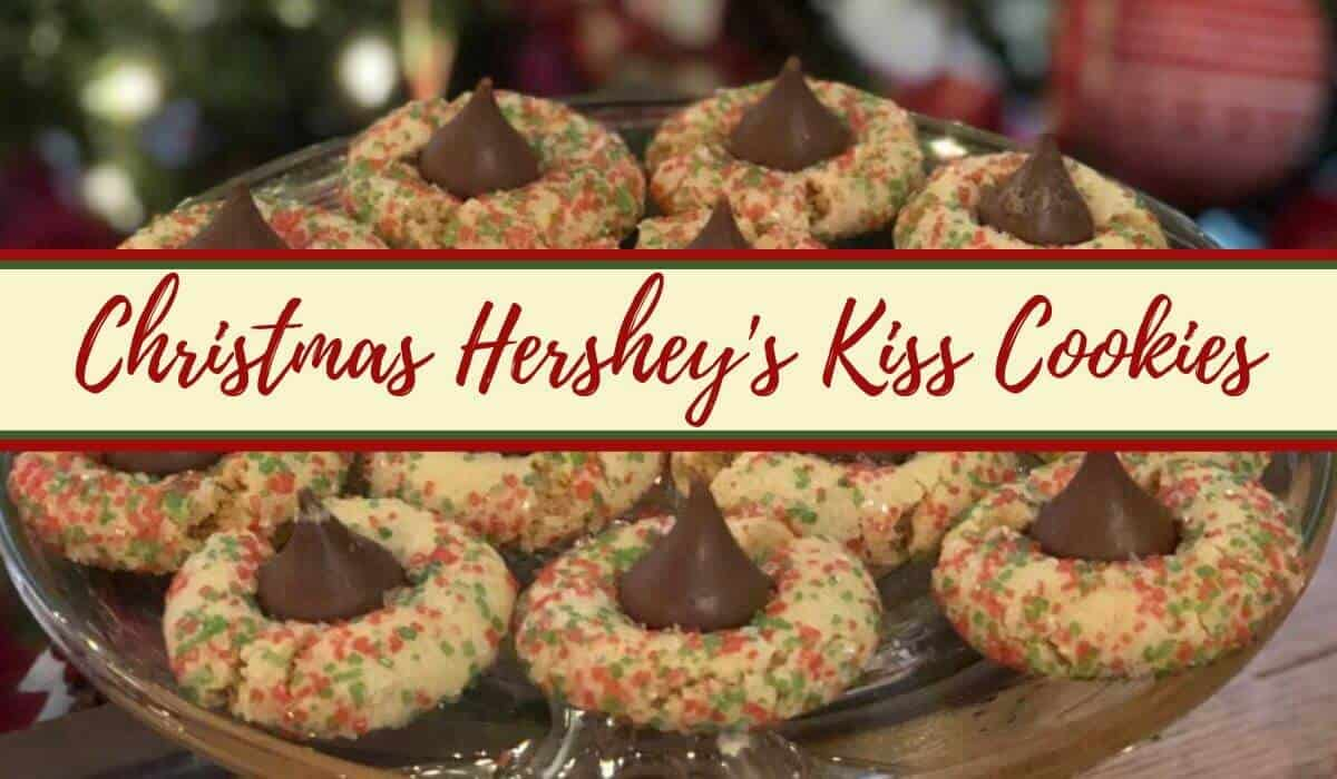 Christmas decorated hershey kiss peanut butter cookies on a glass plate in front of Christmas tree