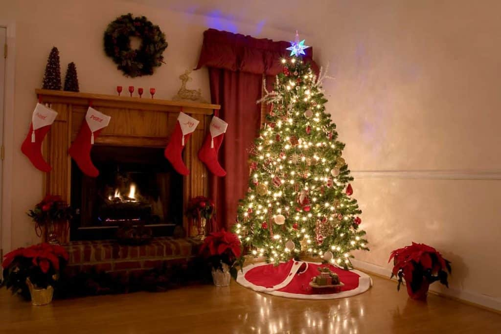 Decorated Christmas Tree in the corner of living room next to the mantle with stockings and wreath