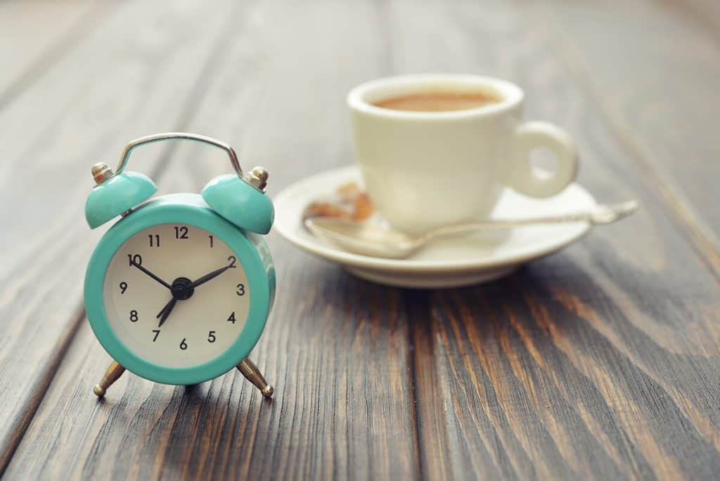 alarm clock on a wooden table with a coffee cup in the background