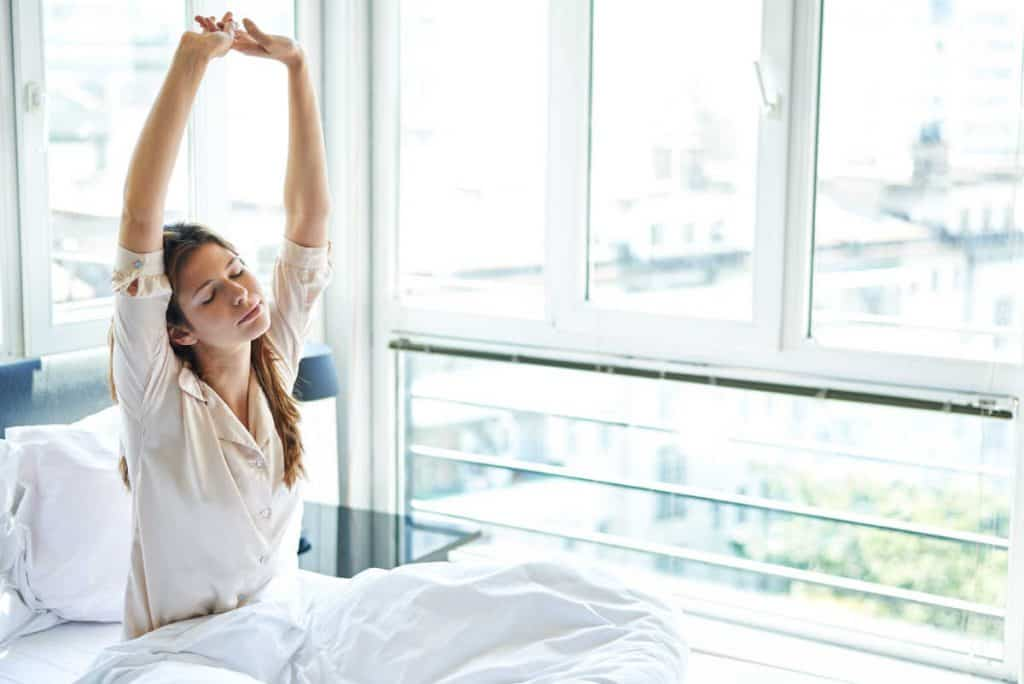 woman waking up in bed in the morning and stretching