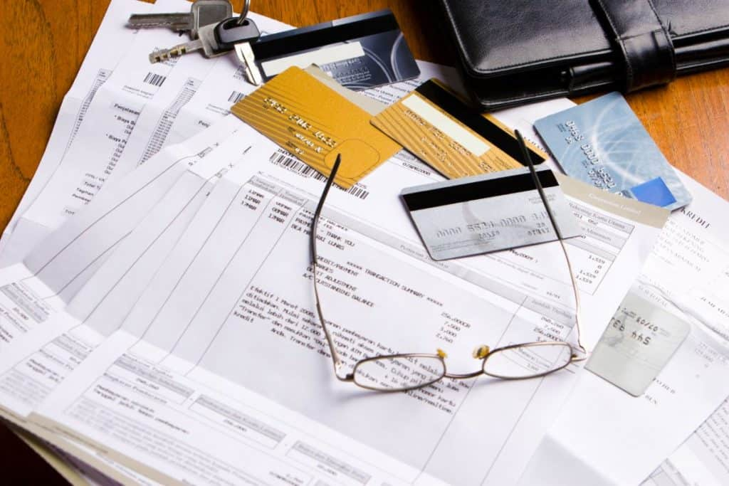 Stack of bills and credit cards with reading glasses on top