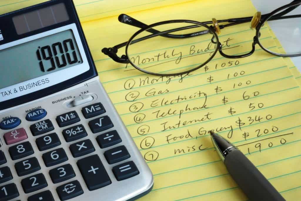 Calculater, ink pen, reading glasses and notepad with budget written out