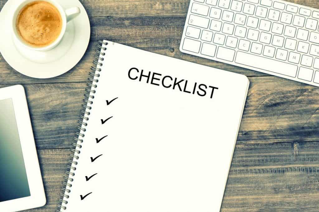 Checklist in a notebook on a desk with laptop and coffee
