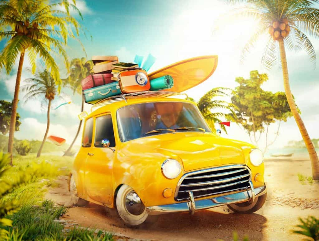 Yellow car packed for beach with suitcases and surfboards on top