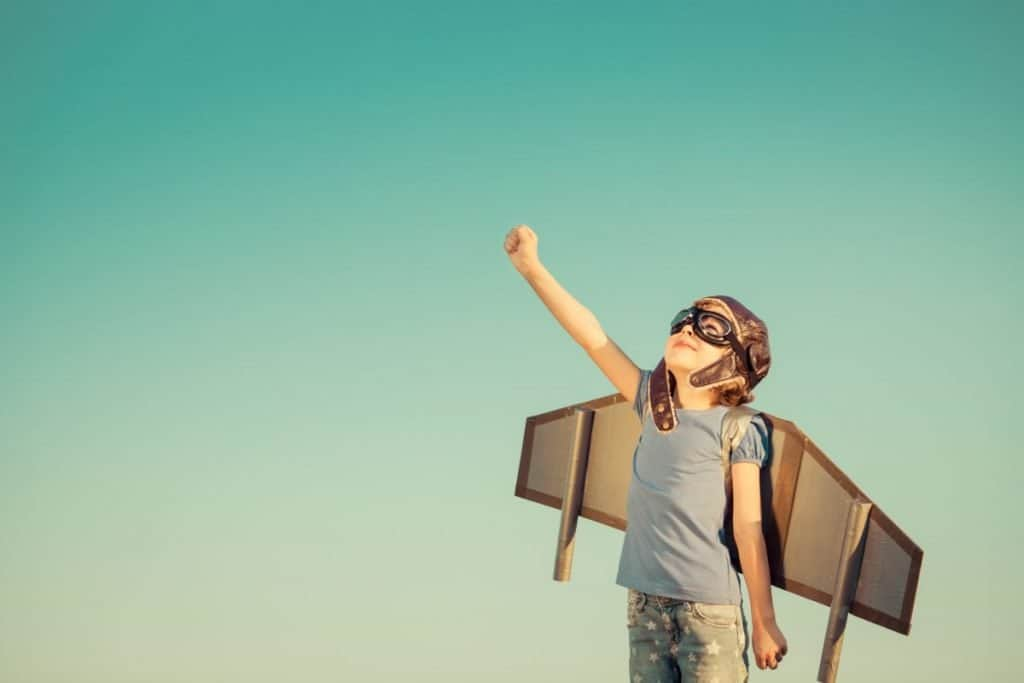 little girl with flight goggles and helmet on with cardboard wings strapped to her