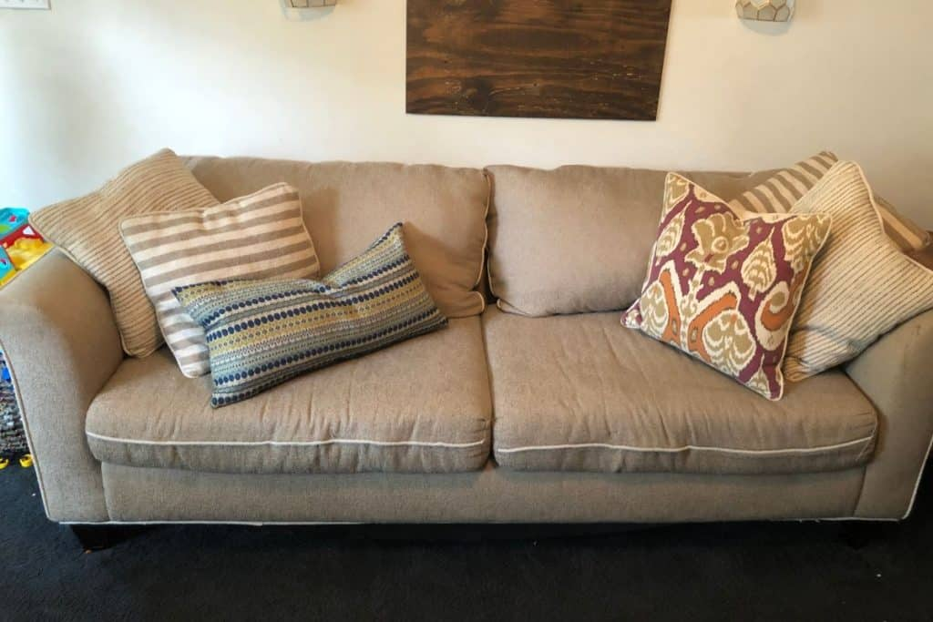 Couch with both cushions restuffed and repaired with colorful throw pillows