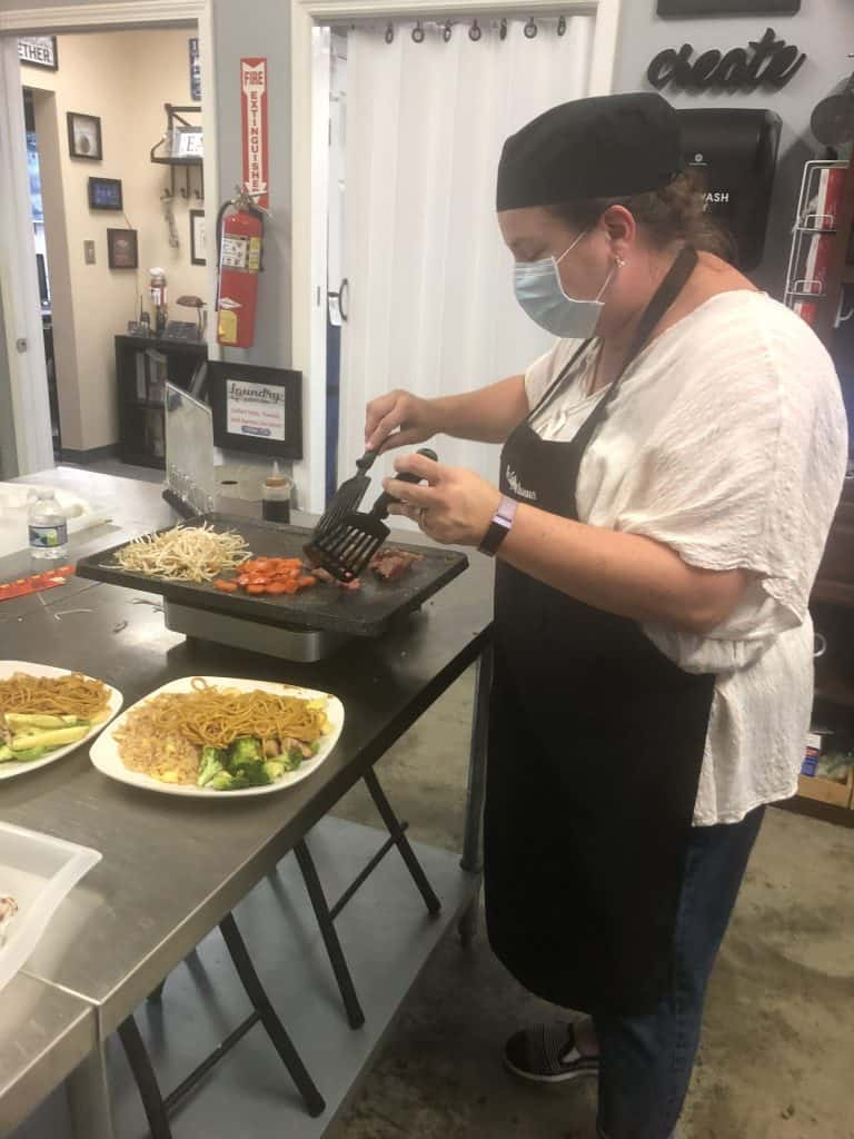 woman in chef's hat with apron in cooking class making hibachi dinner
