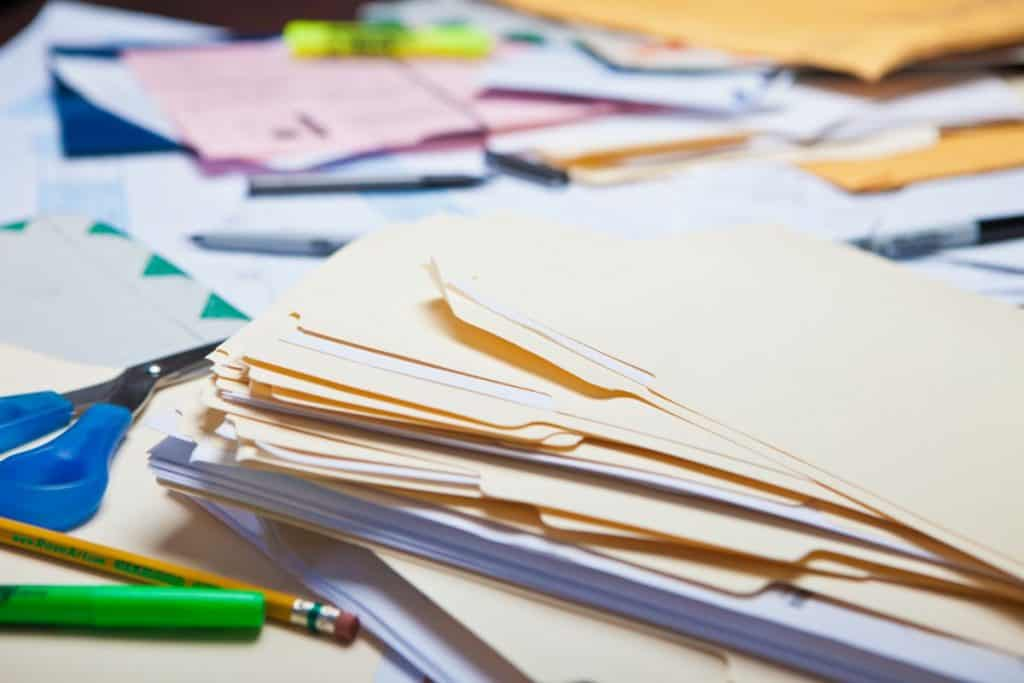 files and papers strewn all over a desk