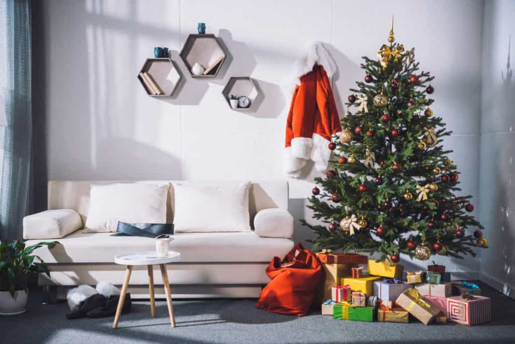 Christmas tree in living room with santa's coat hanging on wall