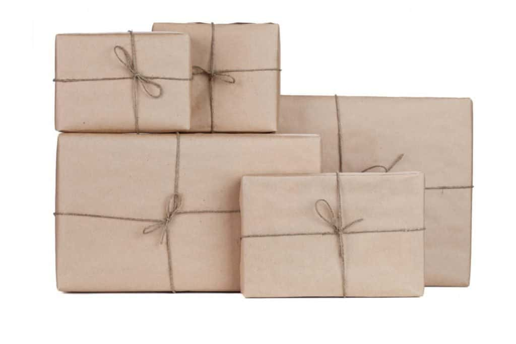 Different sixed boxes wrapped in brown craft paper with twine bows