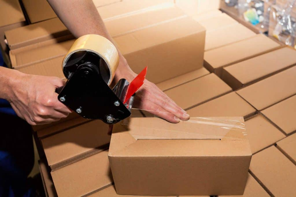 Packing tape gun closing shipping boxes
