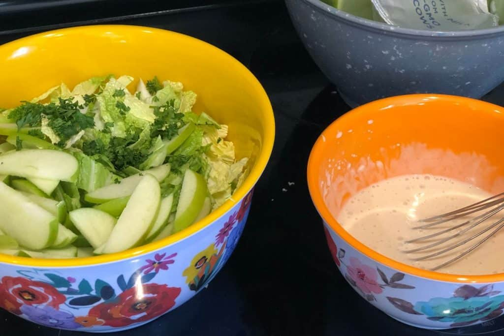 bolw of coleslaw dressing with a whisk next to dry bowl of coleslaw with apples and cabbage