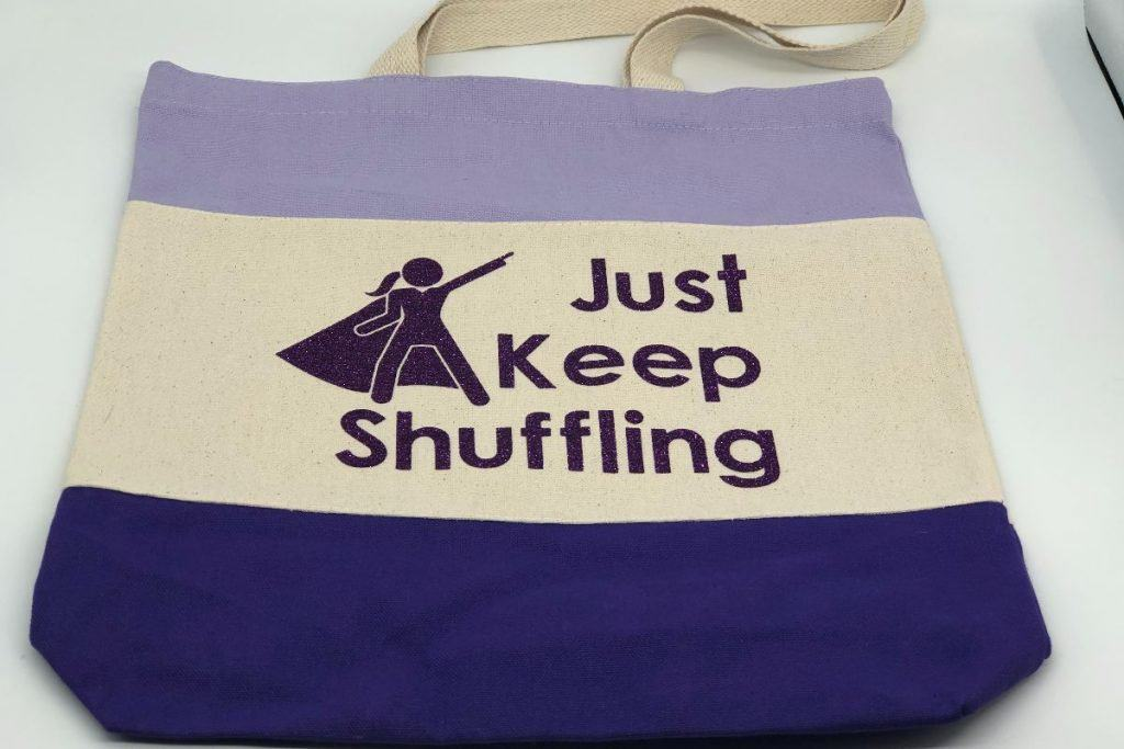 Purple colorblock canvas bag with a Just Keep Shuffling logo with a supermom in purple glitter lettering