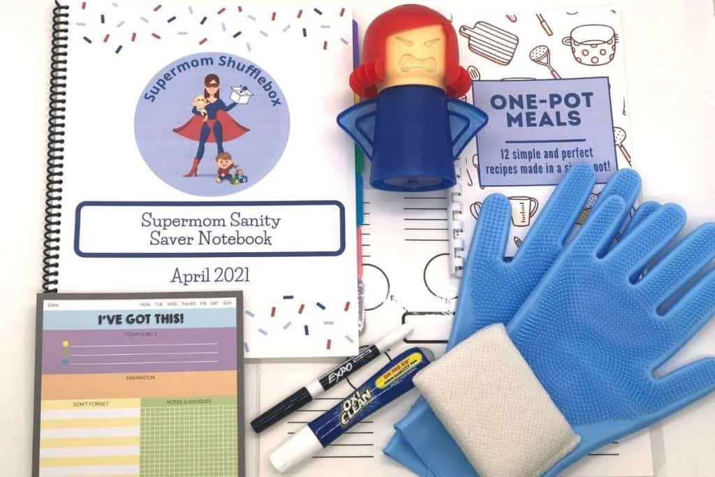 Supermom Shufflebox items in flat lay array, including a mad mama cleaner, cleaning gloves, oxyclean pen, expo marker, scotchbrite sponge, notepad, cookbook, mind map and notebook