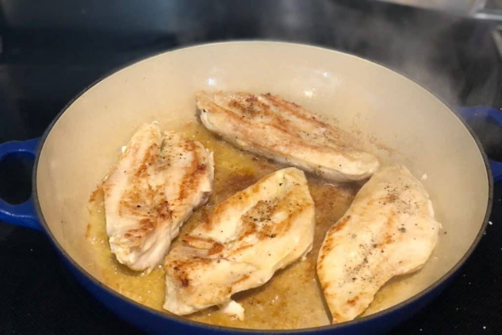 One-Pot Chicken Gnocchi Bake with chicken breasts sauteeing on stove