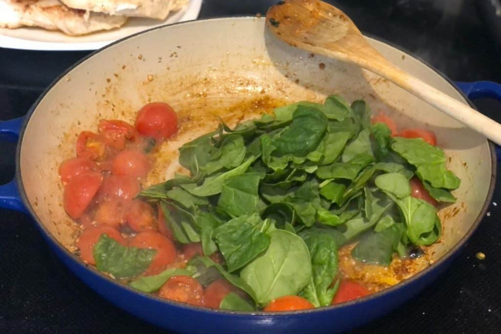 One-Pot Chicken Gnocchi Bake fresh spinach added to pan on stove