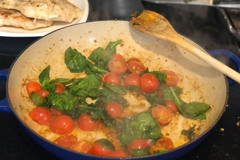 One-Pot Chicken Gnocchi Bake sauteeing spinach and tomatoes on the stove