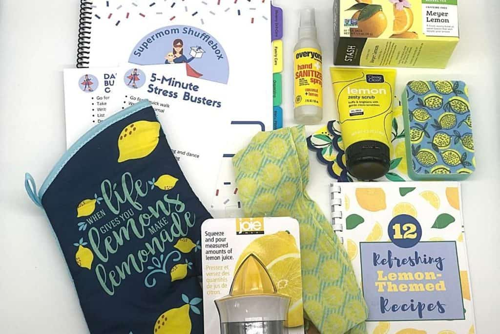 Supermom ShuffleBox Monthly Content Reveal flat lay photo with lemon tea, lemon scrub, lemon sponge, lemon sqeeze, lemon spray, lemon scarf, lemon potholder and notebook and cookbook