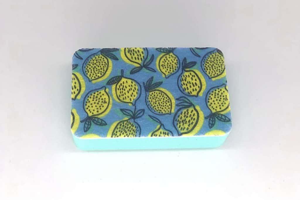 blue kitchen sponge with lemons designed all over it