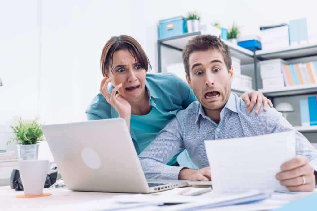 Couple looking at bills with horrified looks on their faces