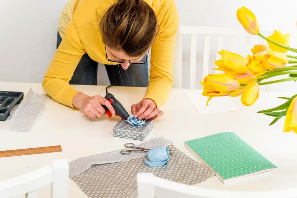 woman in yellow sweater using hot glue gun to finish a gift she's made