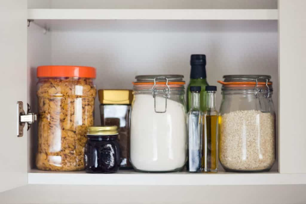 pantry shelf with jars full of oatmeal, sugar and corn flakes