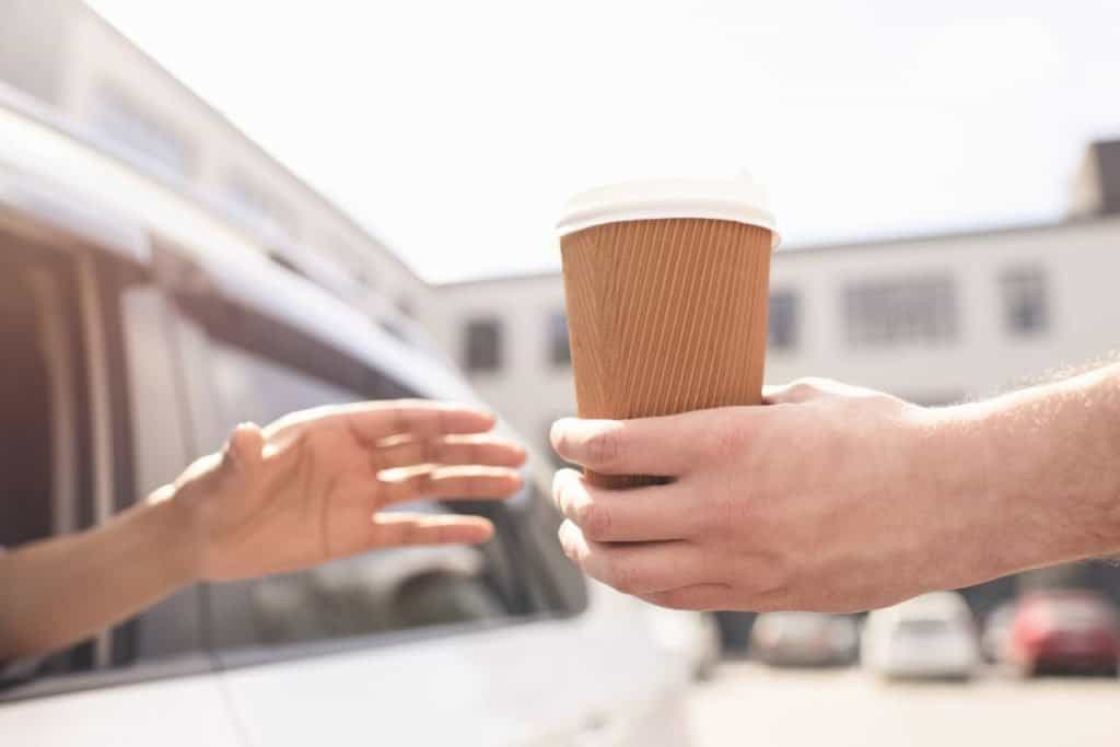 Woman in drive through being handed a to-go cup of coffee