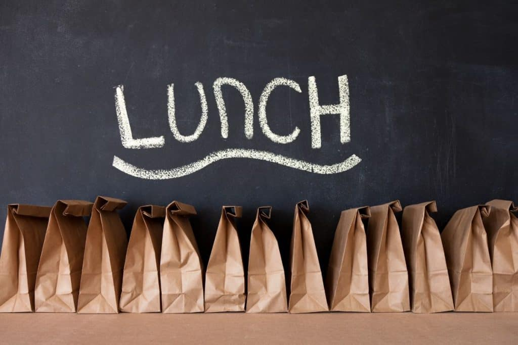 a row of brown paper bag lunches with a chalkboard with lunch written behind them