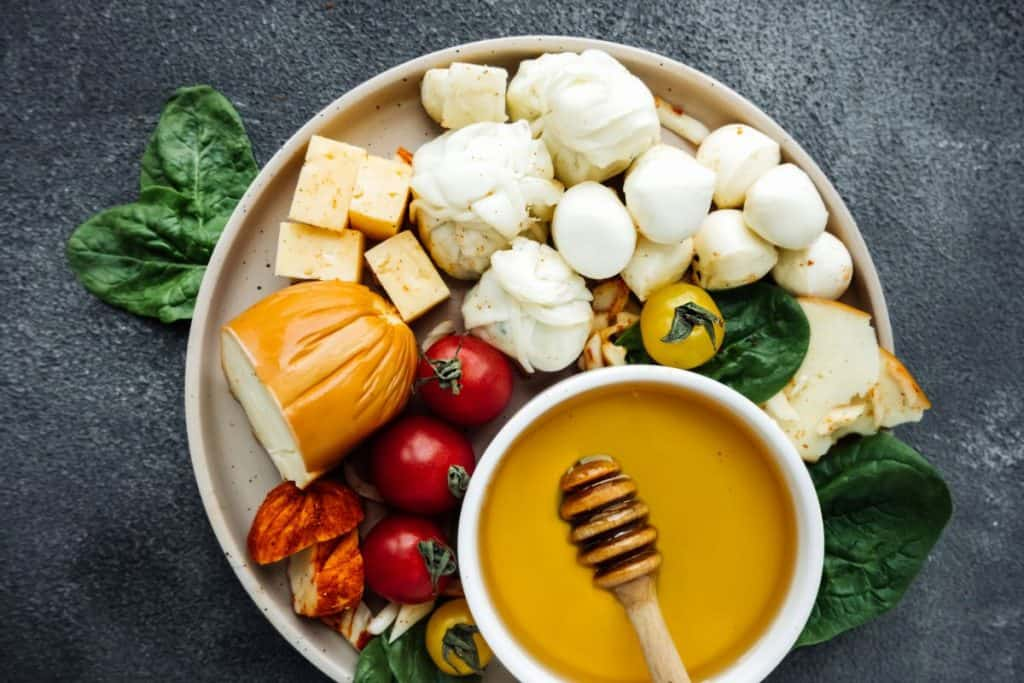 vegetarian platter with honey, bread, cheese and tomatoes