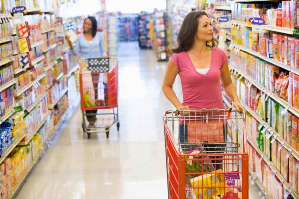 2 women in grocery store aisle shopping seperately