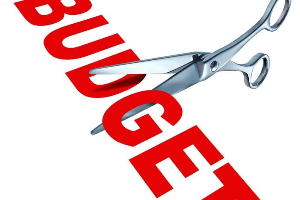 """The word budget in bold red letters with a pair of silver scissors cutting it to """"cut the budget"""""""