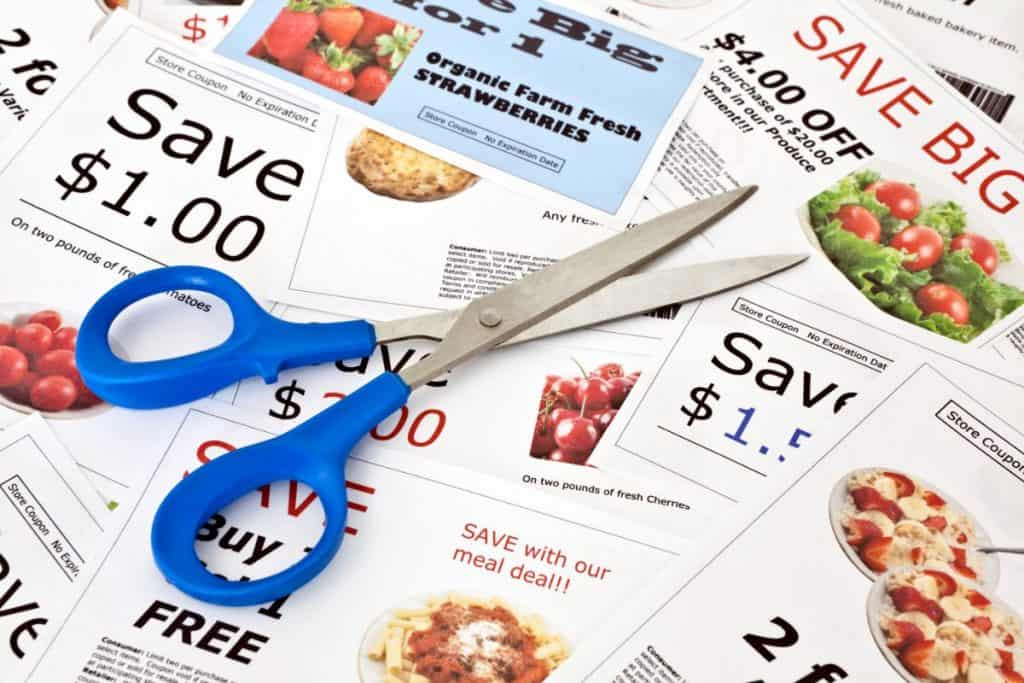 pair of scissors with blue handles sitting on top of a pile of clipped coupons