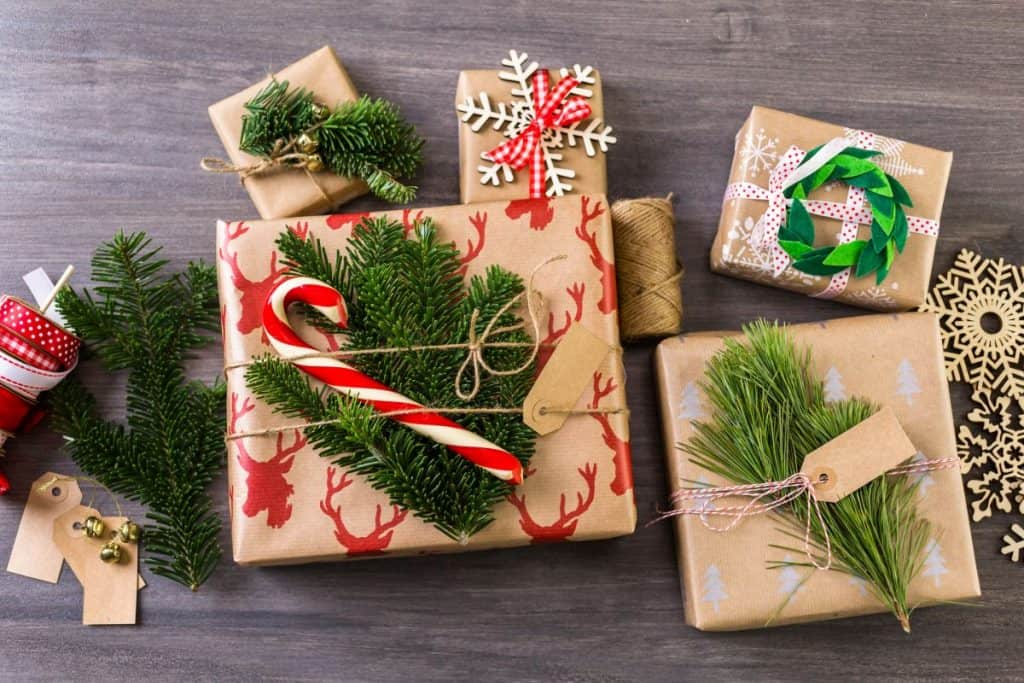 Christmas presents wrapped in paper with pine garland decoration on them