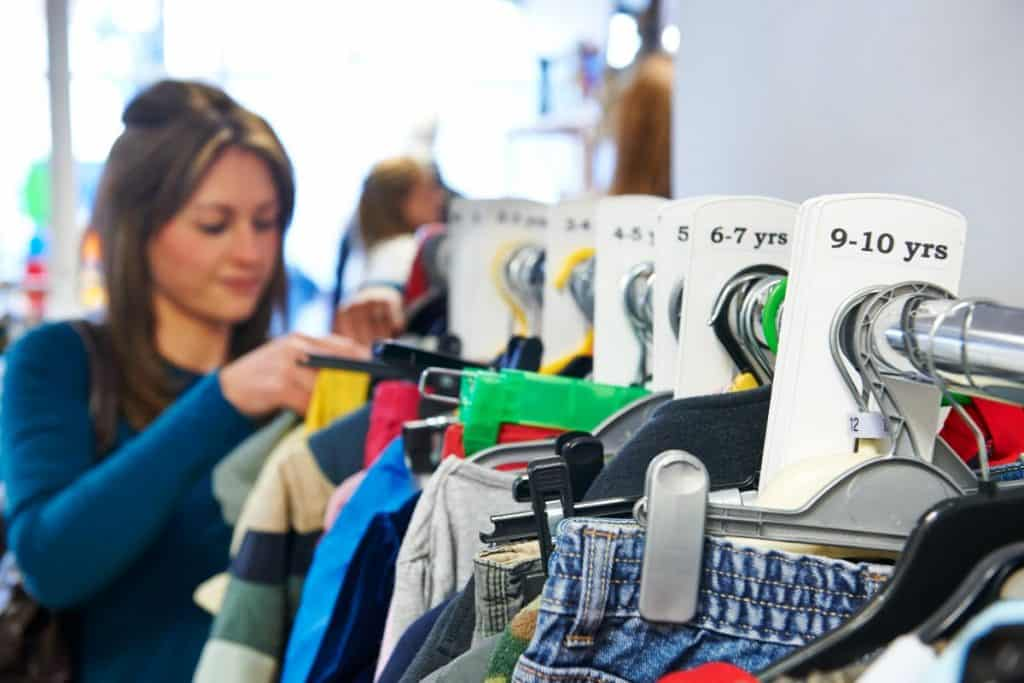 Woman shopping at a secondhand store for kids clothes