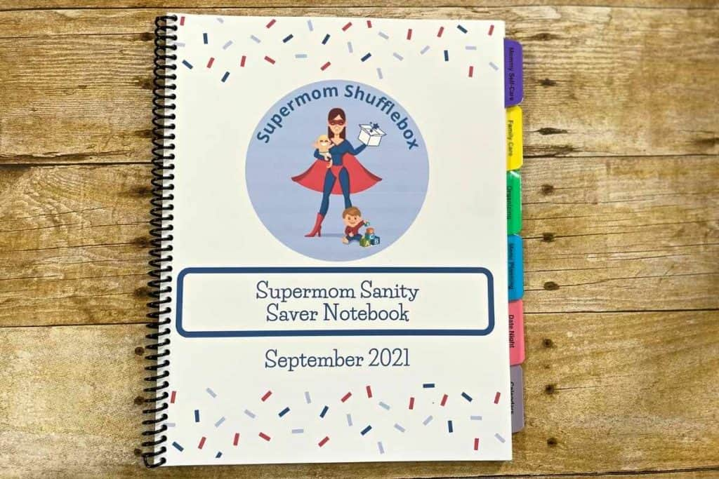 Monthly Supermom Sanity Saver WOrkbook, spiral bound on a wooden table