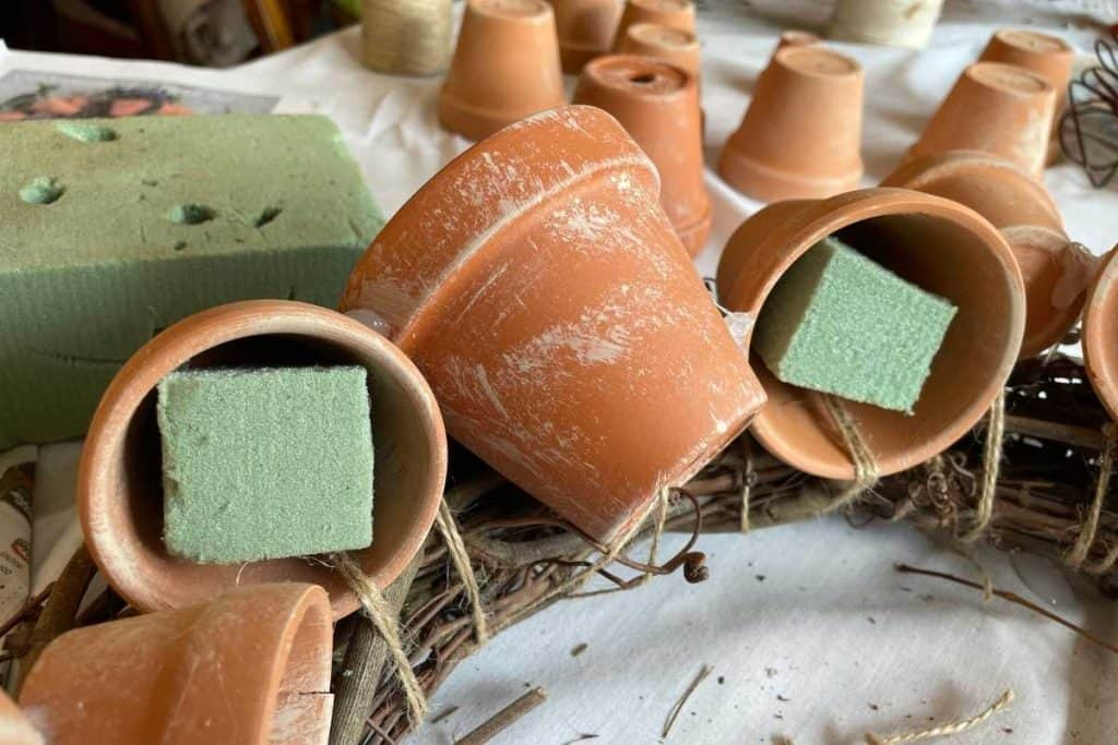 close up of green floral styrofoam being inserted into 2 terracotta pots for Fall DIY Wreath project