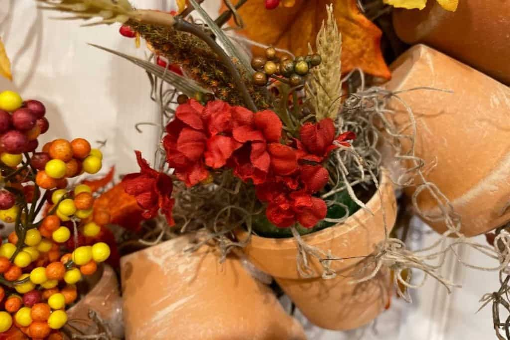 Fake Fall flowers in a terracotta pot for Fall DIY Wreath project