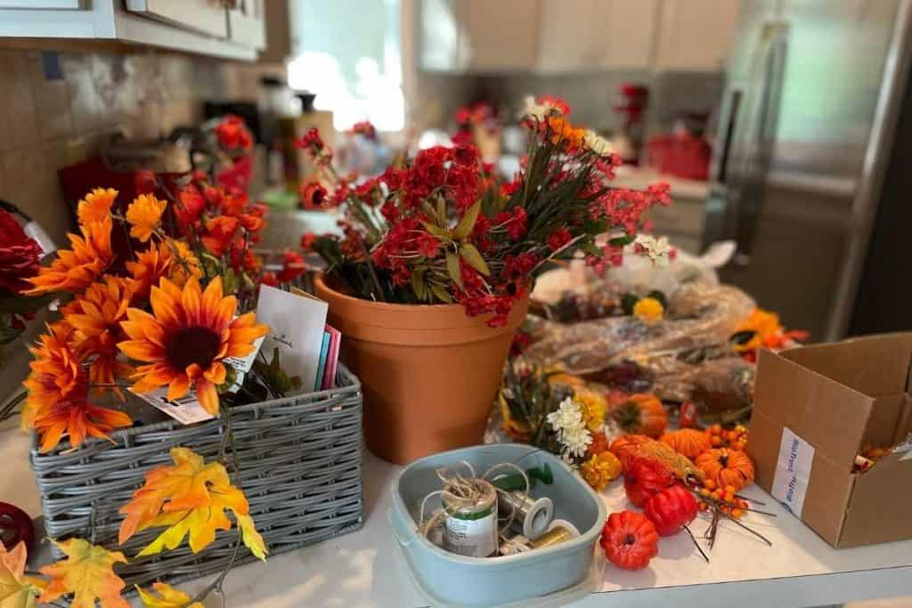 Table full of Fall themed artificial flowers and pumpkins