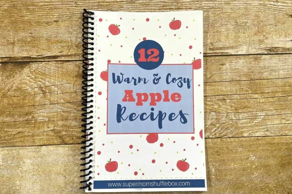 a spiral bound Warm and Cozy Apples recipe book on a wooden table