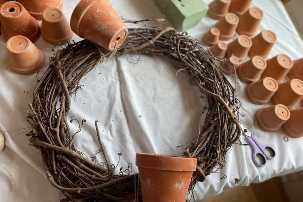 Terracotta pots tied to a grapevine wreath for Fall DIY Wreath project