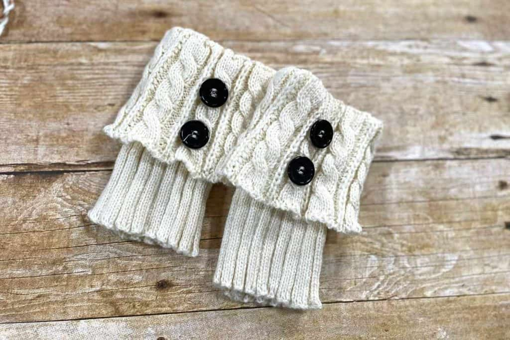 cream colored cable knit boot socks with buttons on a wooden table