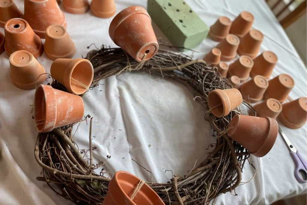6 multi-size terracotta pots tied to a grapevine wreath for Fall DIY Wreath project